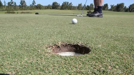 прокатка : A golf ball is putted by a player into the hole on a golf green.