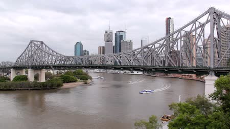 engineered : BRISBANE, AUSTRALIA - SEPTEMBER 28 2011: The iconic Story Bridge spanning the Brisbane River in Brisbane Australia with a city cat ferry. Construction of the bridge began on May 24 1935 and has become the citys greatest tourist attraction. Stock Footage