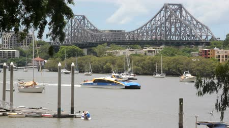 cascos : BRISBANE, AUSTRALIA - January 7 2013: City Cat passes by the Story Bridge. A tourist attraction, the city cat ferry service began in 1996 and now has 13 vessels and are named after aboriginal places.