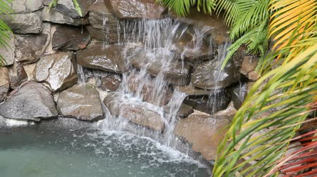 waterfall cascading into pool : Water falling into stone bowls in a garden water feature.