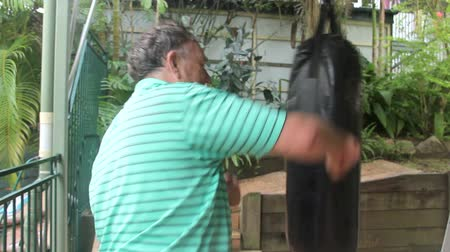 belting : Middle aged man works out with a punching bag. Stock Footage