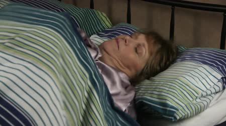 cochilando : Middle aged woman lying in bed turns over in her sleep.