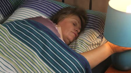 cochilando : Contented middle aged woman lying in bed sleeping turns the lamp on and wakes up.