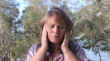 rubs : Middle aged woman outside with headache rubs her temples and head.