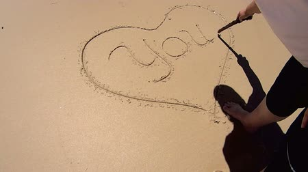 adore : Love heart drawn in the sand on a beach with a wooden stick.