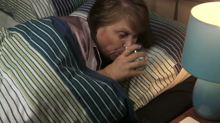cochilando : Middle aged woman lying in bed sleeping turns the lamp on and has a glass of water.