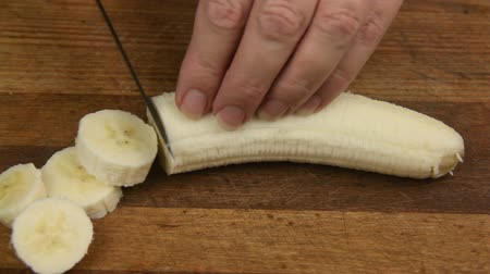 banany : Slicing a fresh banana on a wooden cutting board. Wideo