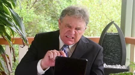 overwrought : Mid shot of a mature businessman who is distraught and upset sitting in a chair on a verandah.