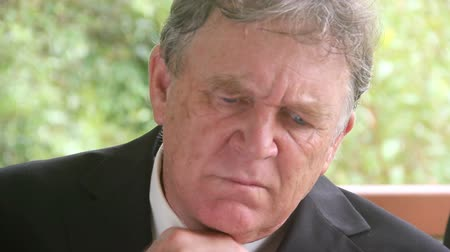 zoufalý : Medium close up of a mature businessman who is frustrated and upset sitting in a chair on a verandah. Dostupné videozáznamy