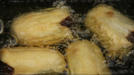 dimsum : Close up of basket of crisp golden dim sums cooking and bubbling in hot oil.