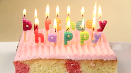 biszkopt : Separate birthday candles on a cake burning which spell out happy birthday. Wideo