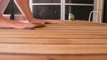 recondition : Person sanding a wooden table by hand to prepare it for varnishing.