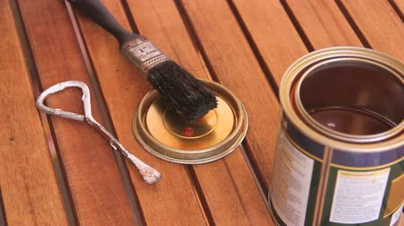 recondition : Brush being taken out of a can of varnish and placed on the lid on a table.