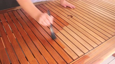 recondition : Person painting a wooden table with varnish with a paintbrush by hand.