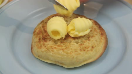 vaj : Curls of butter being placed on a hot English crumpet.
