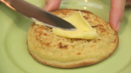 vaj : Butter being spread on a hot English crumpet with a knife then a timelapse of butter melting.