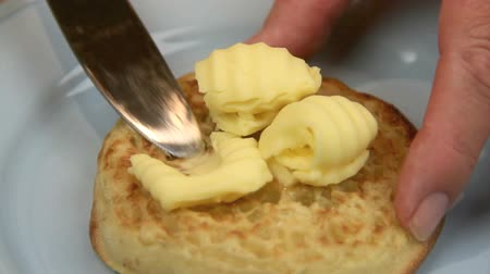 vaj : Curls of butter being being spread on a hot English crumpet with a knife.