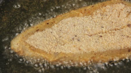 хлеб : Close up pan across a crumbed fish fillet frying in hot oil.