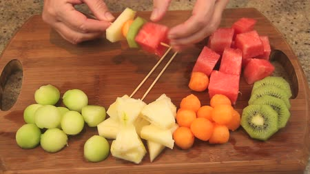 canteloupe : Placing pieces of fresh fruit on a wooden skewer to make fruit kebabs. Stock Footage