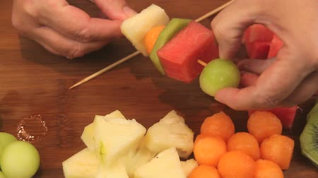 canteloupe : Close up putting pieces of fresh fruit on a wooden skewer to make fruit kebabs.