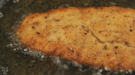 migalhas : Close up pan across a ready crispy crumbed fish fillet frying in hot oil.