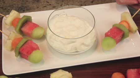 canteloupe : Serving fruit kebabs on a plate with with a yogurt dipping sauce.