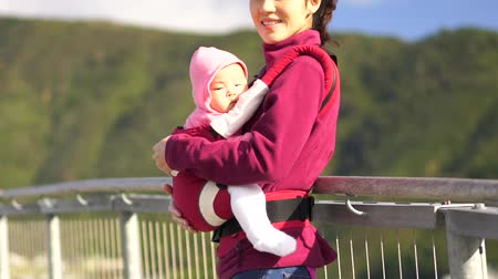 одинокий : Asian mother carrying newborn traveling around