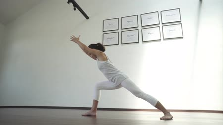 tágas : asian chinese woman in yoga pose in white studio
