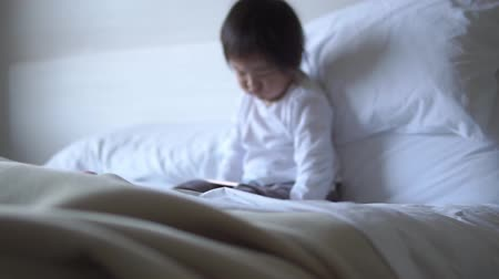boyish : Small Asian chinese toddler sitting on the bed addicted to tablet Stock Footage