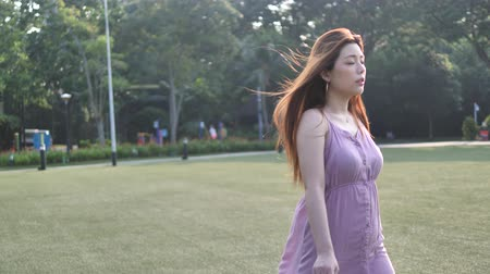 восхищенный : Asian chinese woman in slow motion walking on grass lawn
