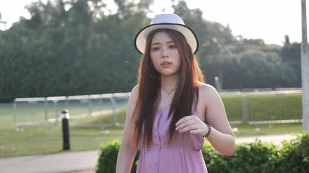 faház : Asian chinese woman in slow motion walking on grass lawn