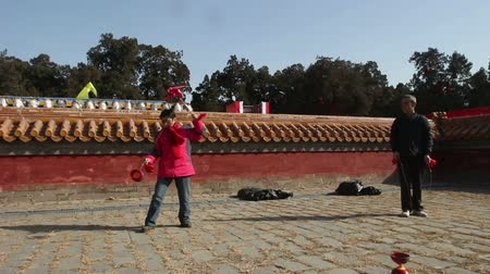 diabolo : Beijing,China-Feb 2, 2014: The old man and woman play diabolo together at temple fair during Chinese Spring Festival in Beijing, China