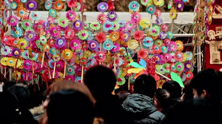 ditan : Beijing,China-Feb 6, 2014: The colorful pinwheel stand and the visitors at Ditan temple fair during Spring Festival in Beijing, China Stock Footage