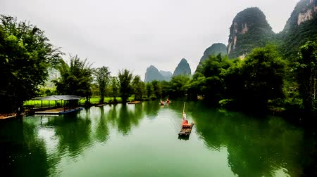 guangxi : Guilin,China-Apr 28,2014:The bamboo raft with visitors goes on the Yulong river in Yangshuo,China Stock Footage