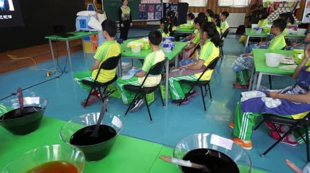 dyeing : Children listening to teacher in a fabric dyeing workshop Stock Footage