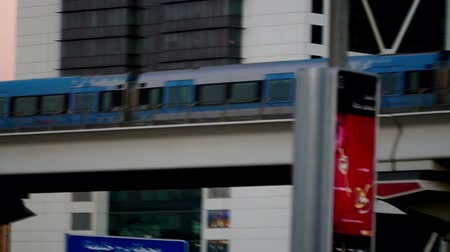 dubaj : A metro train passing before the modern buildings in Dubai, UAE