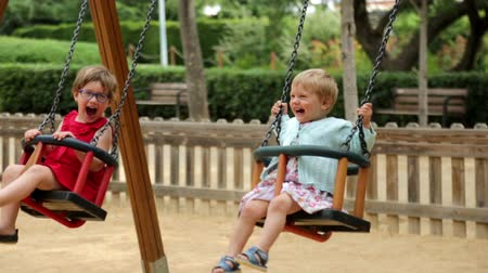 houpavý : Two laughing children on swing in summer park