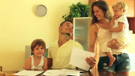 ипотека : Smiling parents and two daughters sitting at table with documents Стоковые видеозаписи