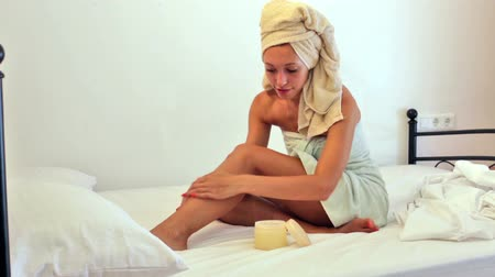 towel : young woman putting cream on feet at home Stock Footage
