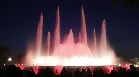 szökőkút : BARCELONA, SPAIN - APRIL 17, 2015: Evening view at colorful vocal fountain Montjuic show and people watching it nearby in Barcelona.  Catalonia Stock mozgókép