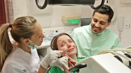 dismay : Dentist, assistant and scared patient at surgery office Stock Footage