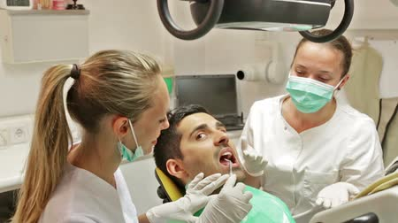 dismay : Portrait of doctor and frightened patient at dental clinic