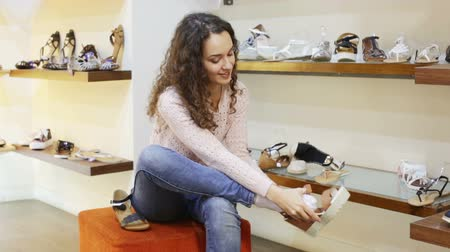 reconcile : woman chooses summer shoes at fashionable shop Stock Footage
