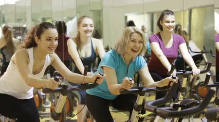 papeteria : Females riding stationary bicycles in modern gym for women