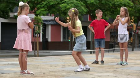 corda : cheerful boy and girls in elementary school age having fun with chinese jumping rope