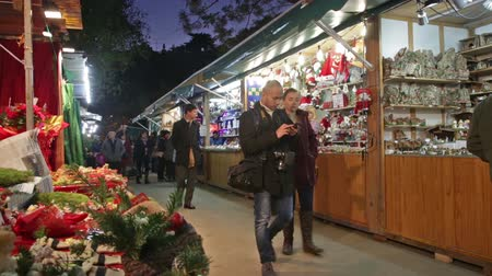 disambiguation : BARCELONA, SPAIN - NOVEMBER 30, 2015: People walking at Christmas market  in evening. Barcelona, Catalonia. Kiosks with Traditional Christmas toys and gifts Stock Footage