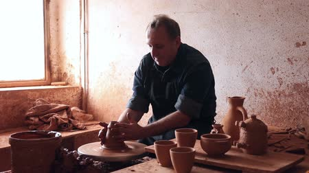 louça de barro : Elderly master among the pottery at the workshop Stock Footage