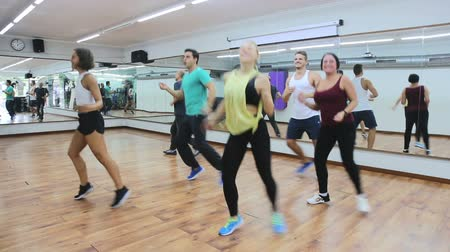 posição : Young positive people learning zumba steps in dance hall