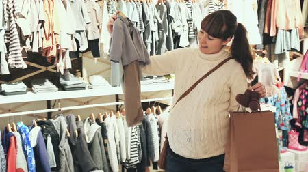 crawlers : Pregnant woman deciding on clothes for baby in children clothes shop Stock Footage