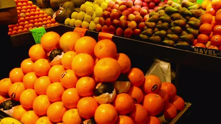 persimmons : BADALONA, SPAIN - MARCH 10, 2017: Fruits and vegetables on spanish market counter, La Salut Municipal market